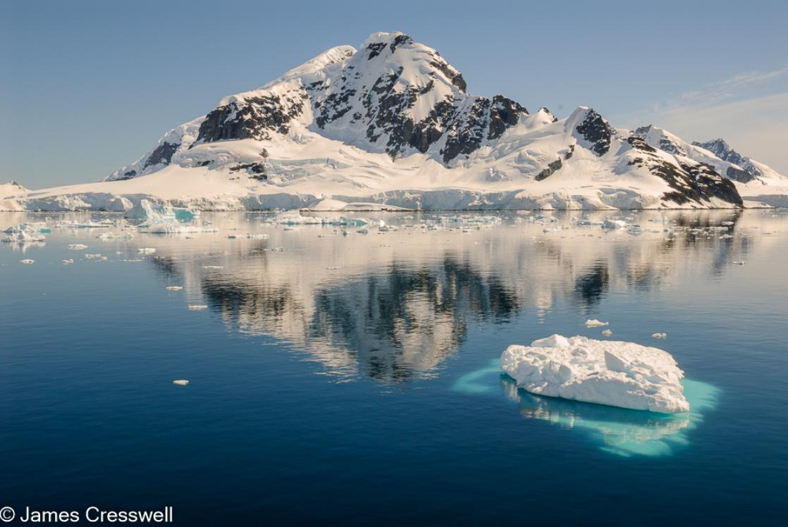 A photograph of a glaciated mountain with in inky blue sea and iceberg in the foreground, taken in Paradise Harbour, Antarctica on a PolarWorld Travel expedition cruise