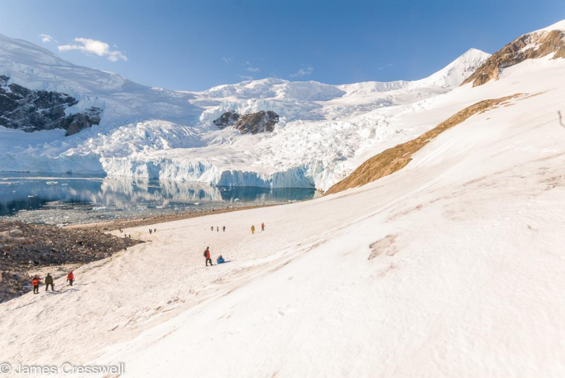 A photograph of people standing in the snow with a glacier behind taken at Neko Harbour, Antarctica, taken on a PolarWorld Travel polar expedition cruise