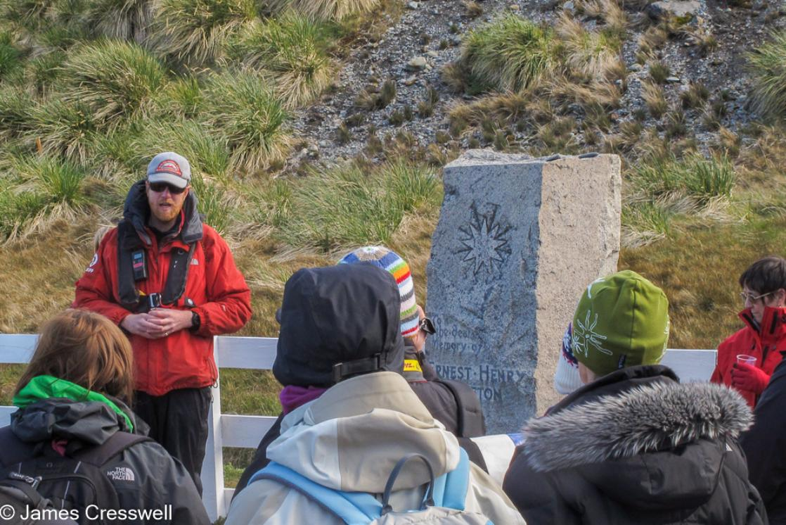 A photograph of James Cresswell Director of GeoWorld Travel & PolarWorld Travel performing a toast to Shackleton at his grave in Grytviken, South Georgia