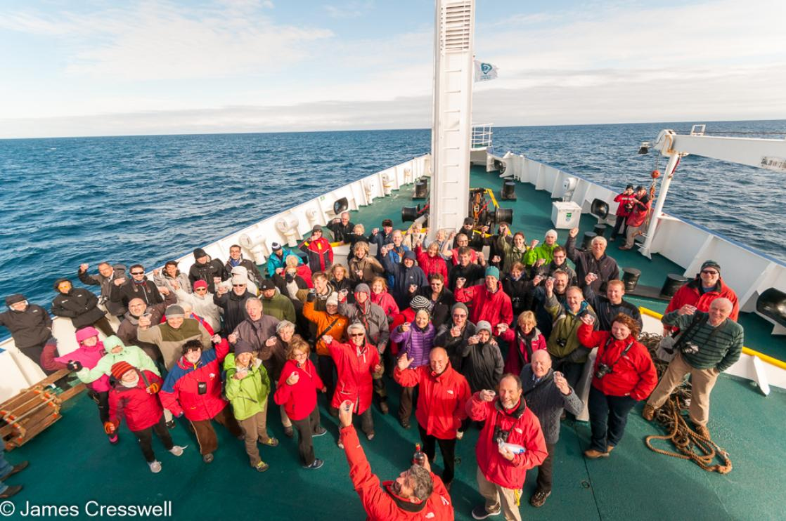 A photograph of a group of people on the bow of a ship, the m/v Plancius, celebrating as they cross the Arctic Circle, taken on a PolarWorld Travel polar expedition cruise