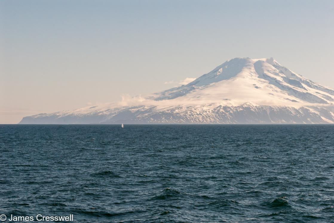 A photograph of Jan Mayen island and Beerenburg volcano with a blue whale blow in the foreground, taken on a PolarWorld Travel, polar expedition cruise