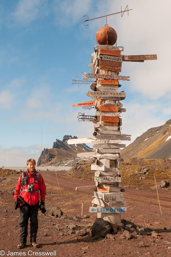 A photograph of James Cresswell Director of GeoWorld Travel & PolarWorld Travel standing next to a large sign post on Jan Mayen