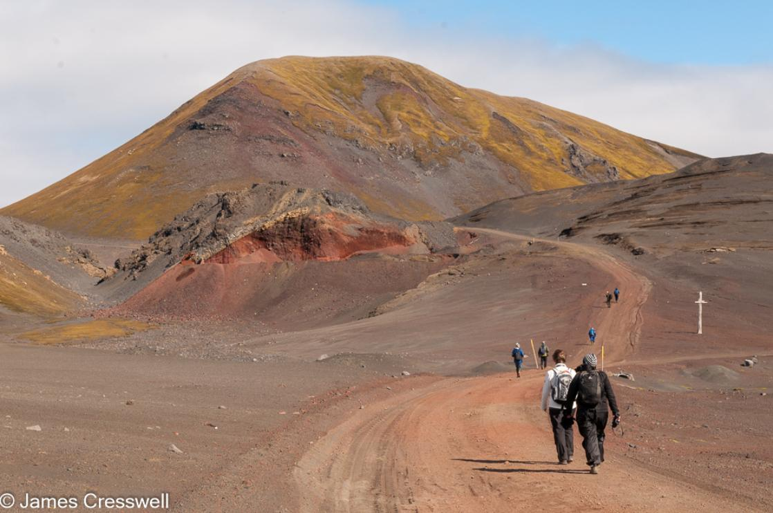 A photograph of people walking in a volcanic landscape on Jan Mayen, taken on a PolarWorld Travel polar expedition cruise